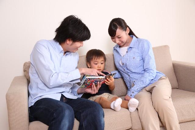 両親が子供に絵本を読み聞かせている